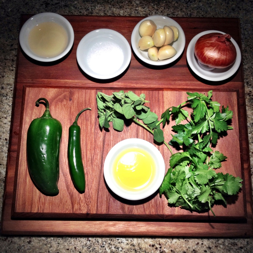 Apple cider vinegar, salt, garlic, shallot, jalapeño pepper, serrano pepper, fresh oregano, flat-leaf parsley, cilantro, olive oil. (Red pepper flake optional, though highly recommended.)